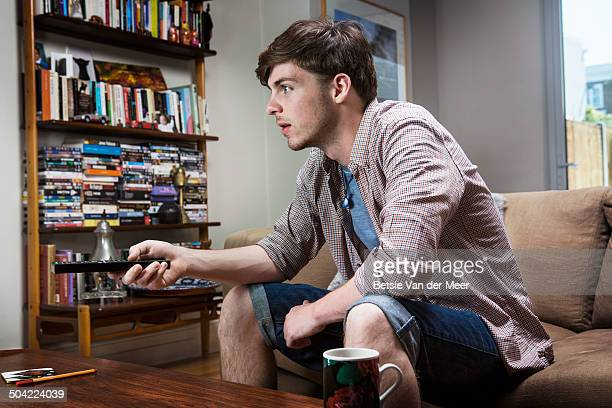 young man watching television at home.