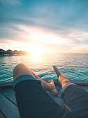 Point of view shot of a young man watching the sunset on an island in the Maldives. Shot from a personal perspective.
