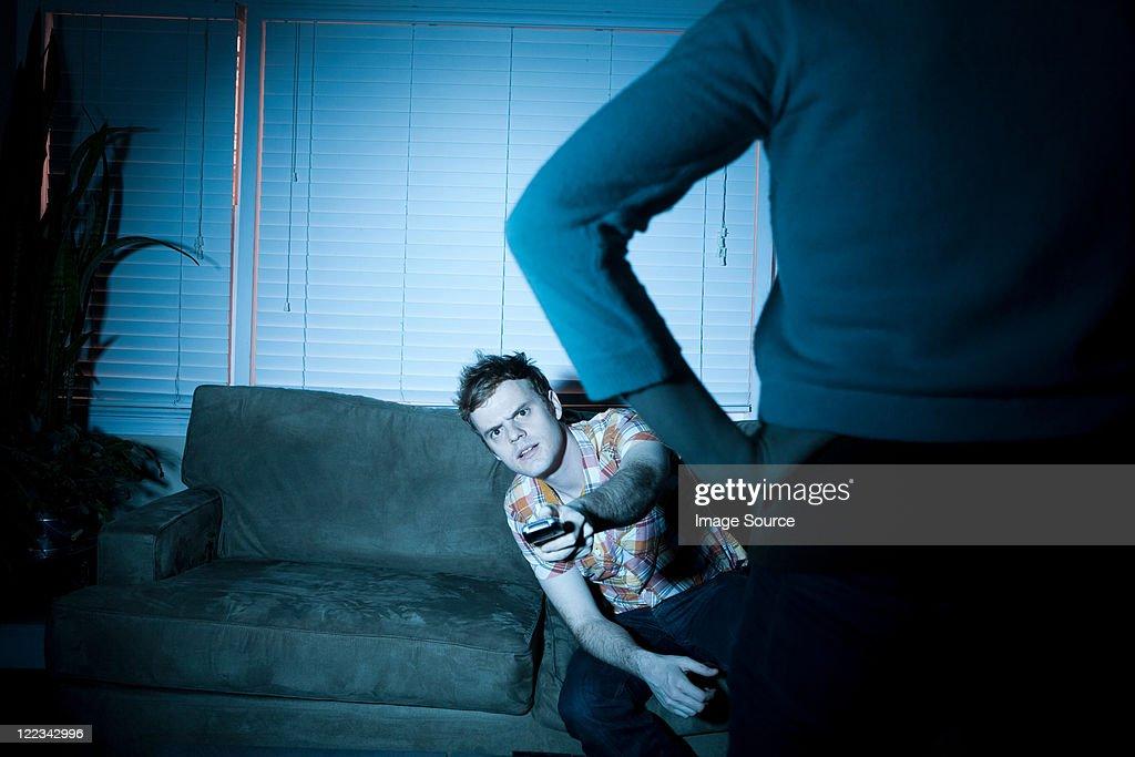 Young man watching tv, woman blocking view : Stock Photo