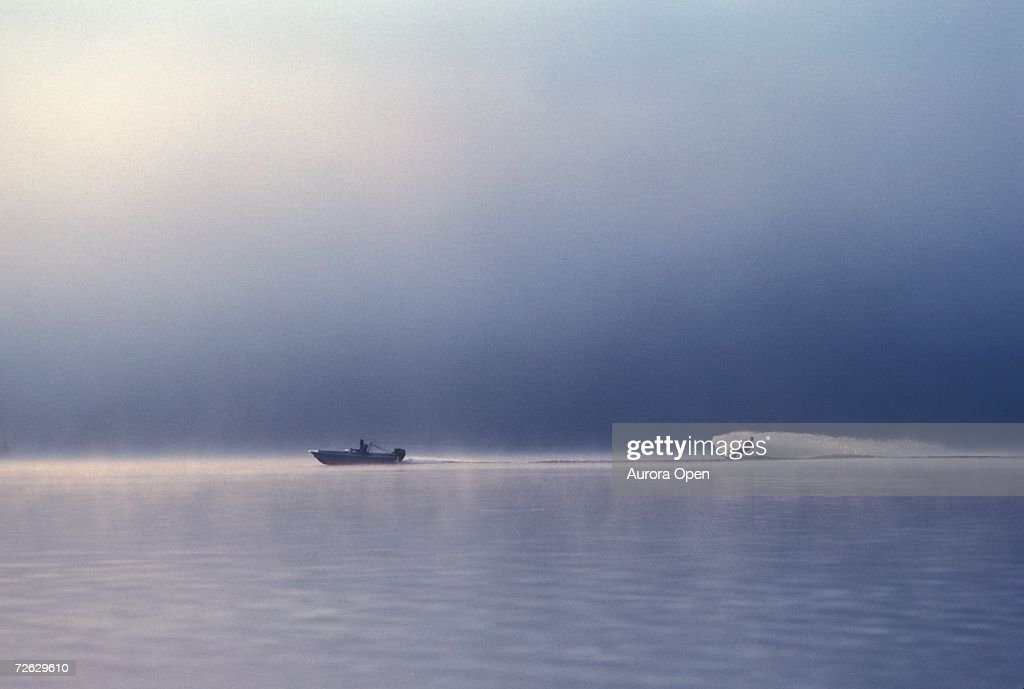 Young man waterskiing in early morning mist on Ottawa River, Ontario, Canada. : Stock Photo