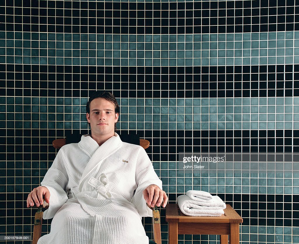 Young man wearing a bathrobe relaxing in spa chair, portrait
