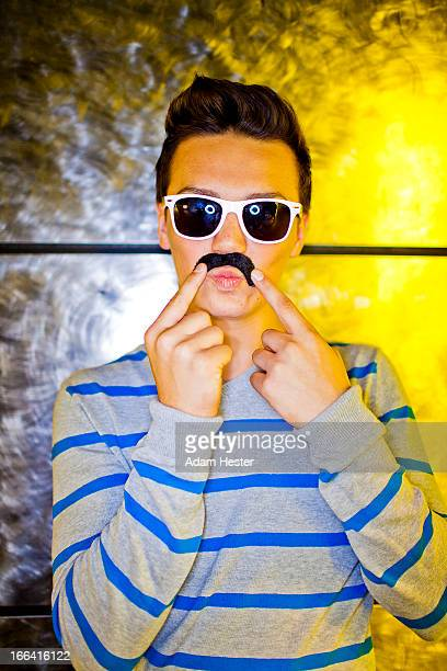 A young man wearing a fake mustache inside.