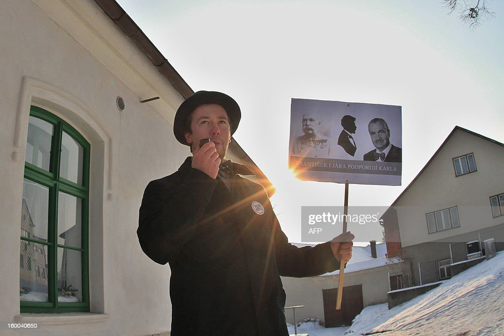 A young man wearing a hat and bow tie, smokes a pipe holds a picture of Czech presidential candidate Karel Schwarzenberg in the village of Sebranice, Czech Republic on January 25, 2013, day of the second round of the first direct Czech presidential election. Sebranice is a village that is known for its the traditional crafts and customs of the pre-war period. Czechs went to the polls to choose a new president between a former communist and a 75-year-old aristocrat whose Sex Pistols-inspired campaign brought the election to life and down to the wire.