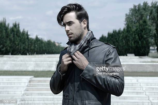 Young man wearing a leather jacket in front of an open staircase, portrait