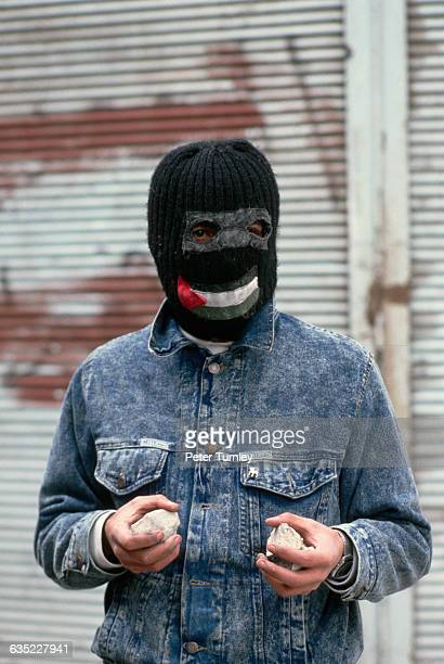 A young man wearing a ski mask with the Palestinian flag sewn over the mouth holding rocks during the Intifada