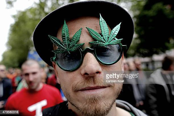 A young man wearing a sun glass marijuana leaf on his head marches in support legalization of marijuana in Germany during the annual Hemp Parade or...