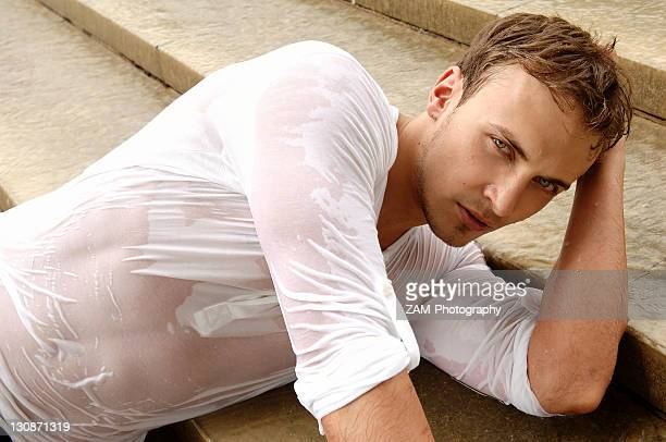 Young man wearing a wet shirt, lying on stairs