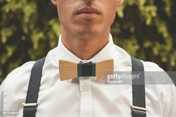 Young man wearing a wooden bow tie, close-up