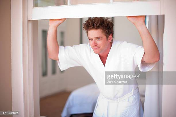 Young man wearing bathrobe by window