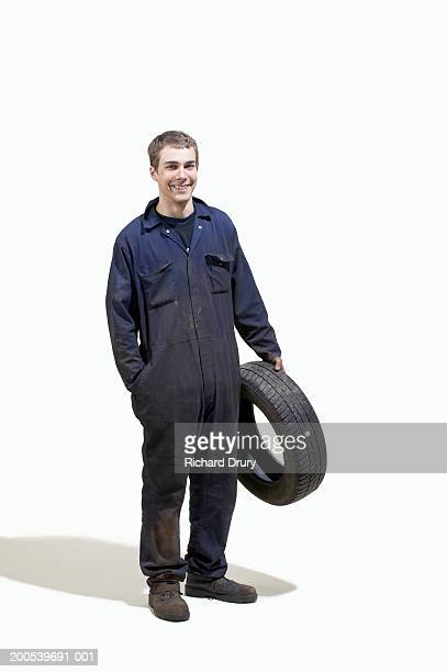 Young man wearing boiler suit holding car tyre, smiling, portrait