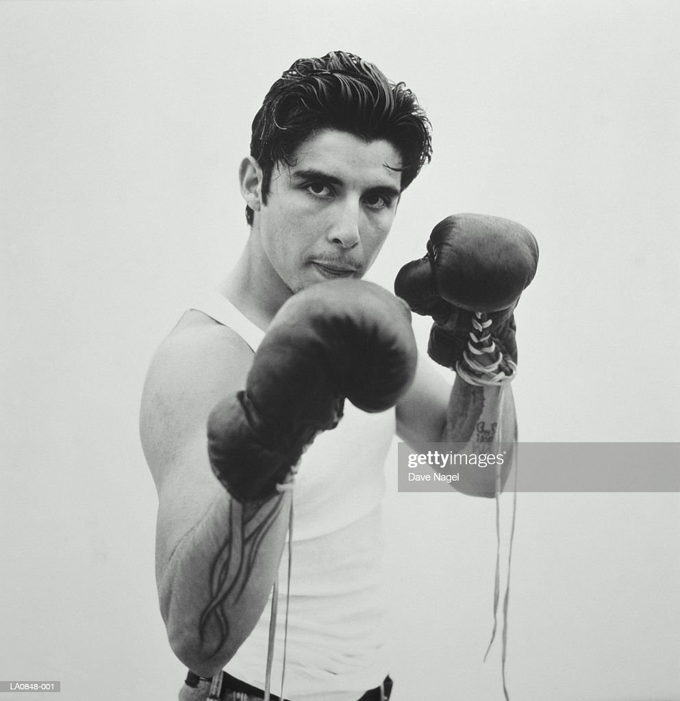 Young man wearing boxing gloves, portrait (B&W) : Stock Photo