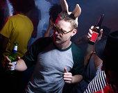 Junger Mann mit Häschenohren Tanzen in Nachtclub