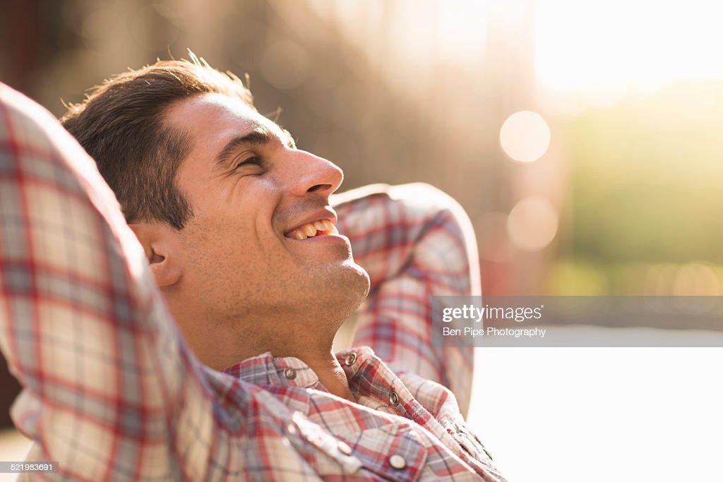 Young man wearing checked shirt, smiling