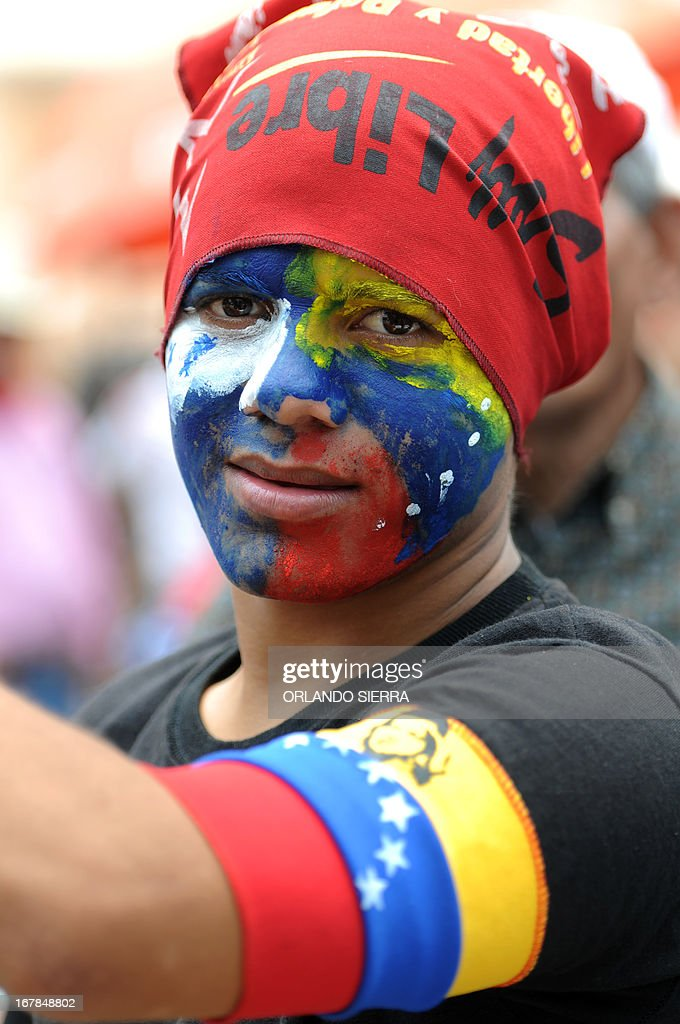 A young man wearing colors of Venezuela and late president Hugo Chavez, during May Day celebrations in Tegucigalpa on May 1, 2013. AFP PHOTO / Orlando SIERRA