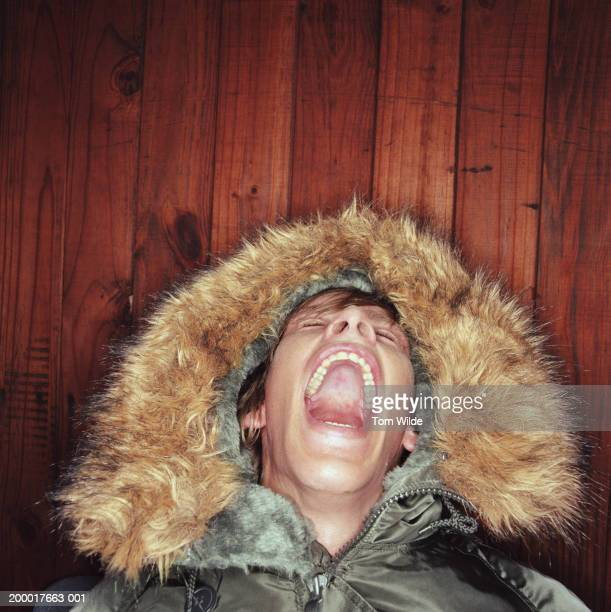 Young man wearing fur trimmed hood laughing, head thrown back