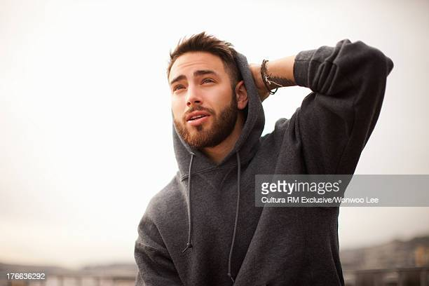 Young man wearing grey hooded top, looking away