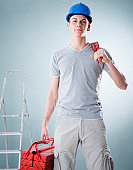 Young man wearing hard hat holding tools