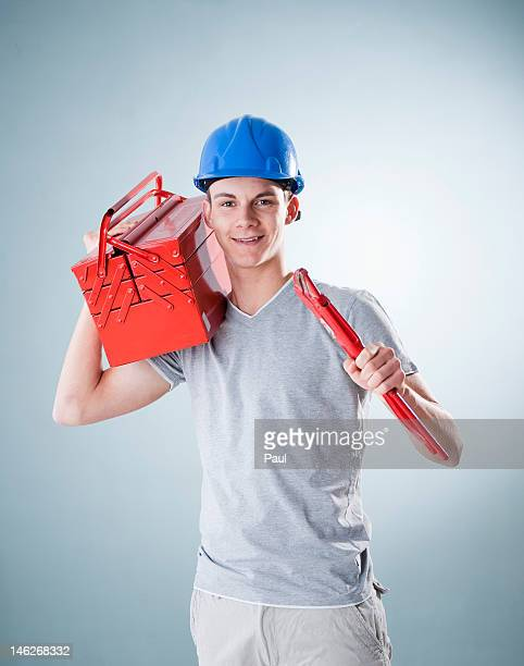 Young man wearing hard hat holding tools, portrait