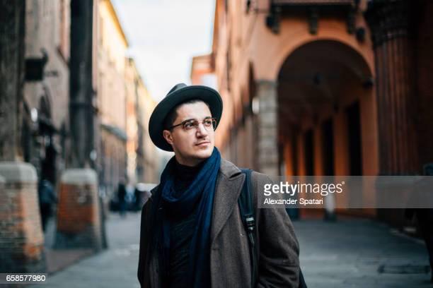 Young man wearing hat and eyeglasses exploring Bologna, Italy