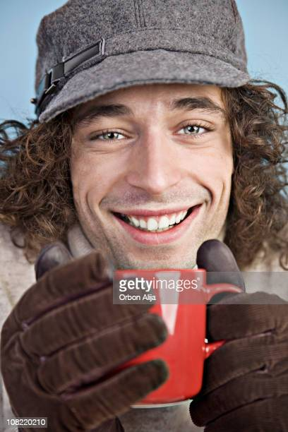 Young Man Wearing Hat and Gloves Holding Coffee Mug