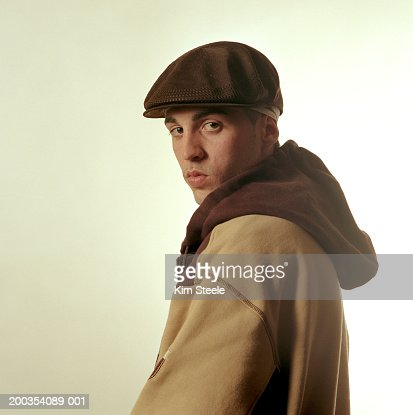 Young man wearing hat and hooded sweatshirt, portrait, side view