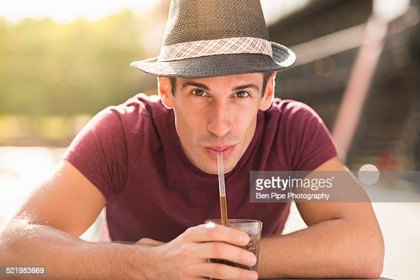 Young man wearing hat drinking through straw
