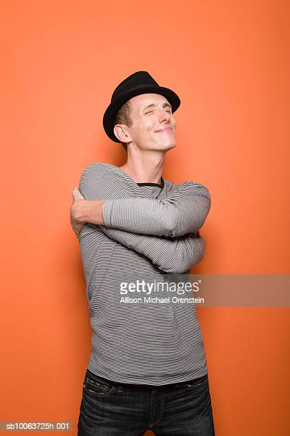Young man wearing hat, hugging self and smiling