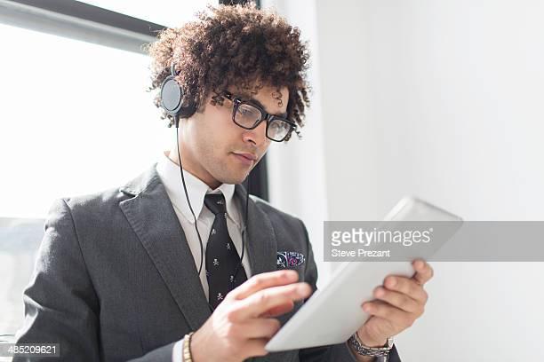 Young man wearing headphones using digital tablet