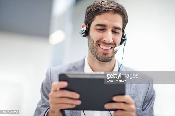 Young man wearing headset using digital tablet