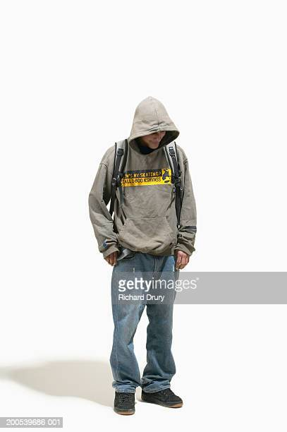 Young man wearing hooded top standing with head bowed