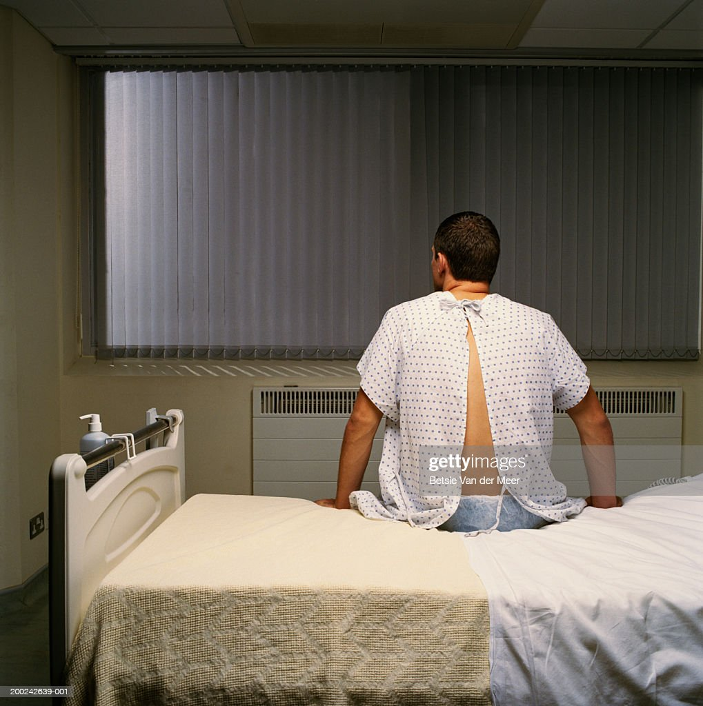 Young man wearing hospital gown, sitting on bed, rear view : Stock Photo