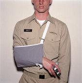 Junger Mann, militärische uniform tragen, arm in sling, mittlerer Teil