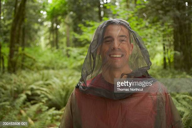 Young man wearing mosquito netting suit in forest, smiling, portrait