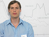 Young man wearing name tag standing in front of chart, portrait