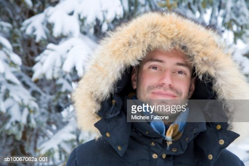 Young man wearing parka, smiling, portrait