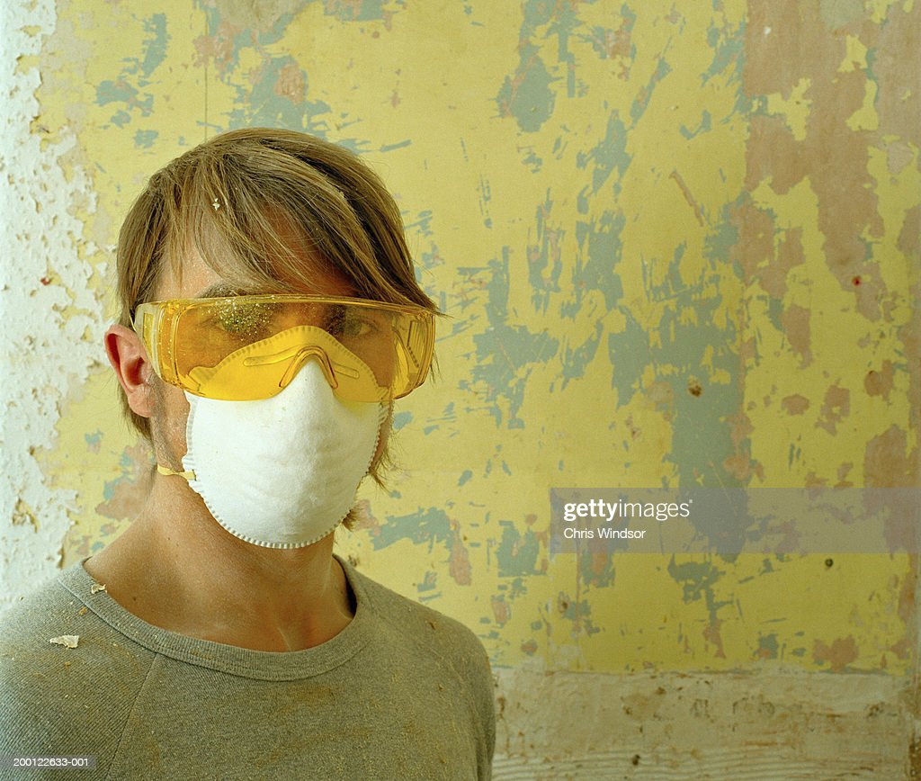 Young man wearing protective goggles and mask, portrait