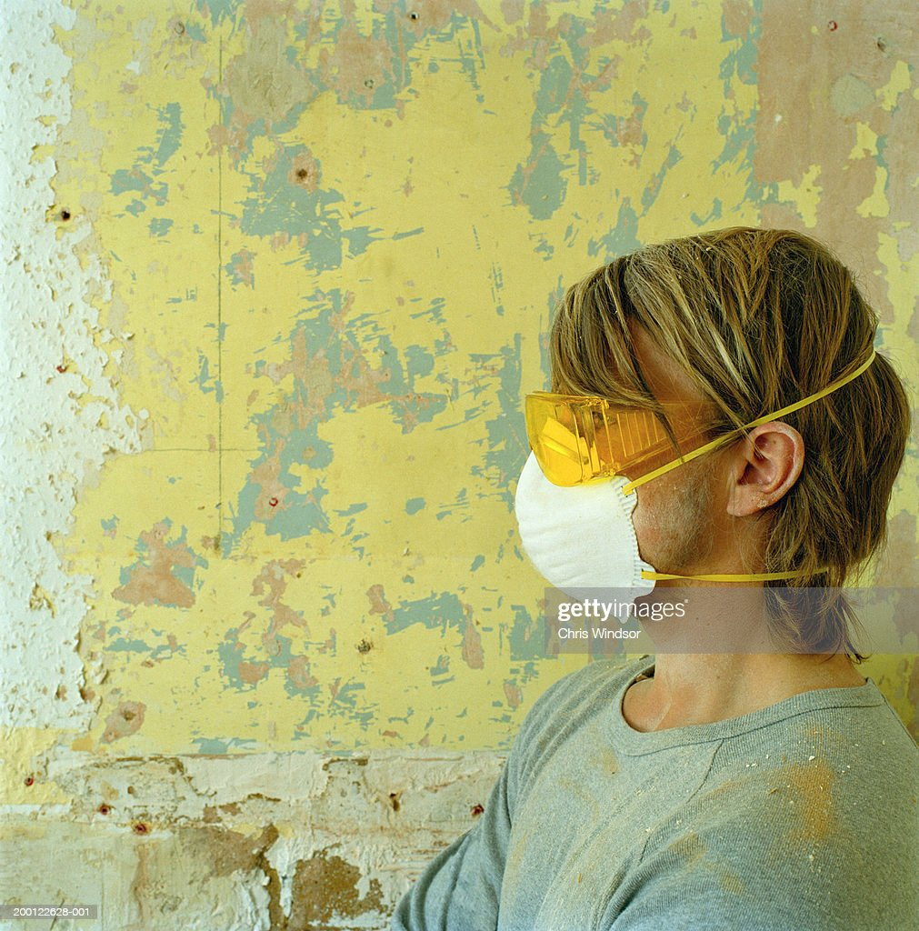 Young man wearing protective goggles and mask, side view