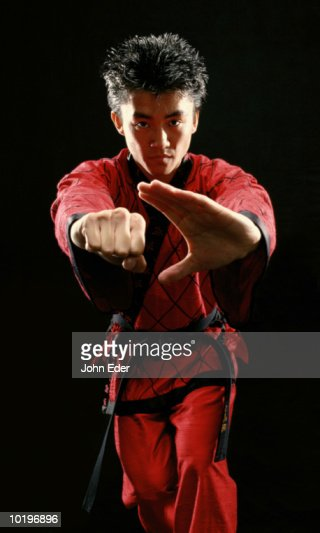Young man wearing red outfit, practicing Kung Fu moves, portrait