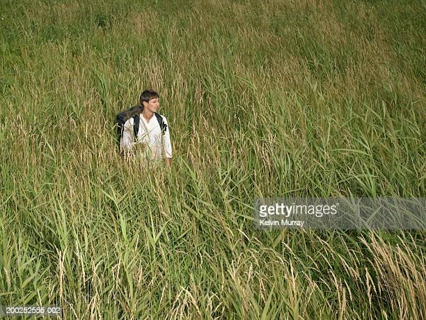 Young man wearing rucksack standing in long grass