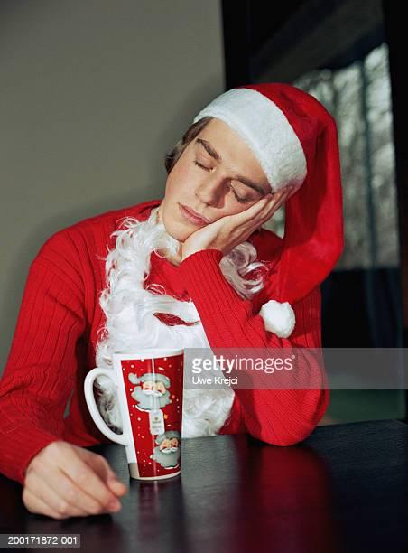 Young man wearing Santa outfit, sleeping at table, cheek on hand