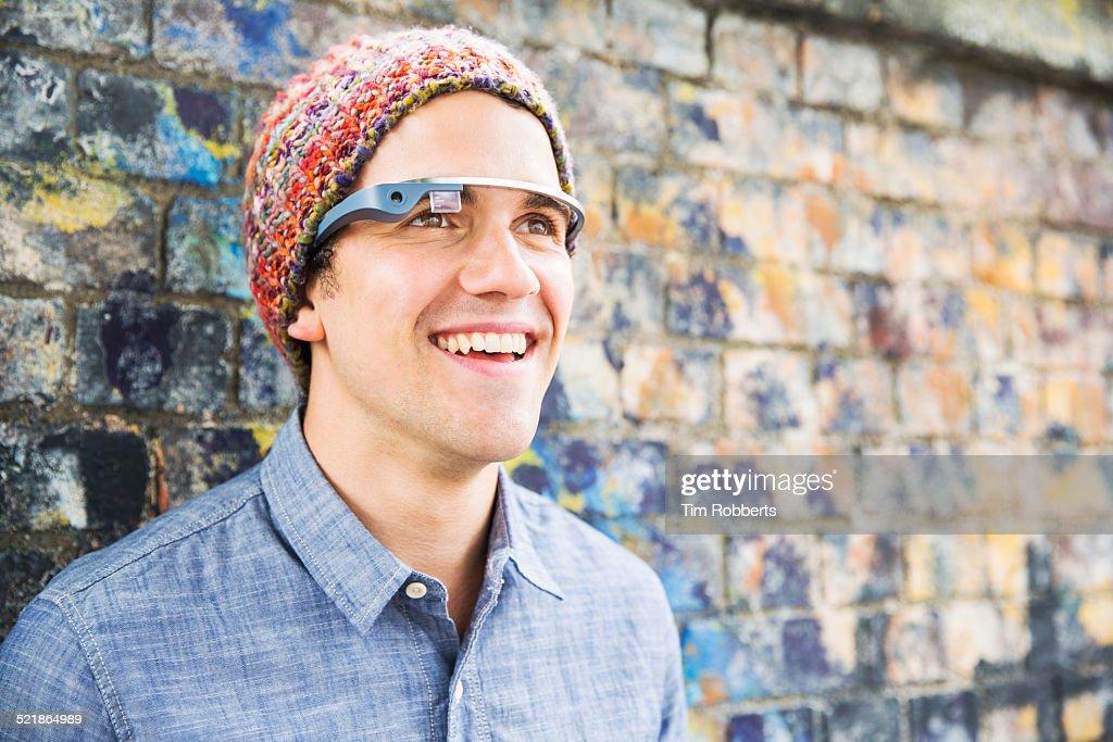 Young man wearing smart glass next to graffiti wal