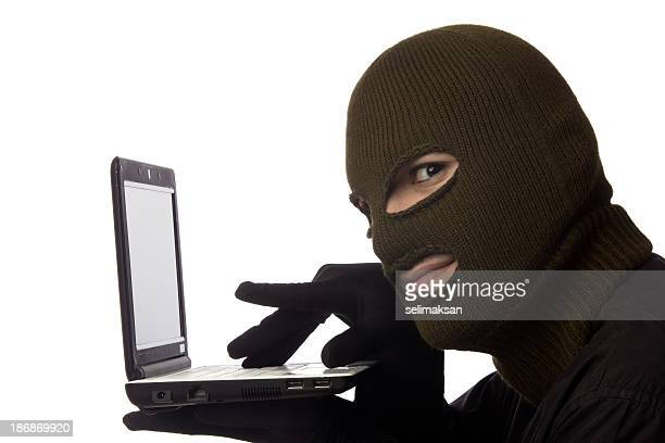 Young man wearing snow mask and posing as computer hacker