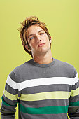 Young man wearing striped jumper against green background, portrait