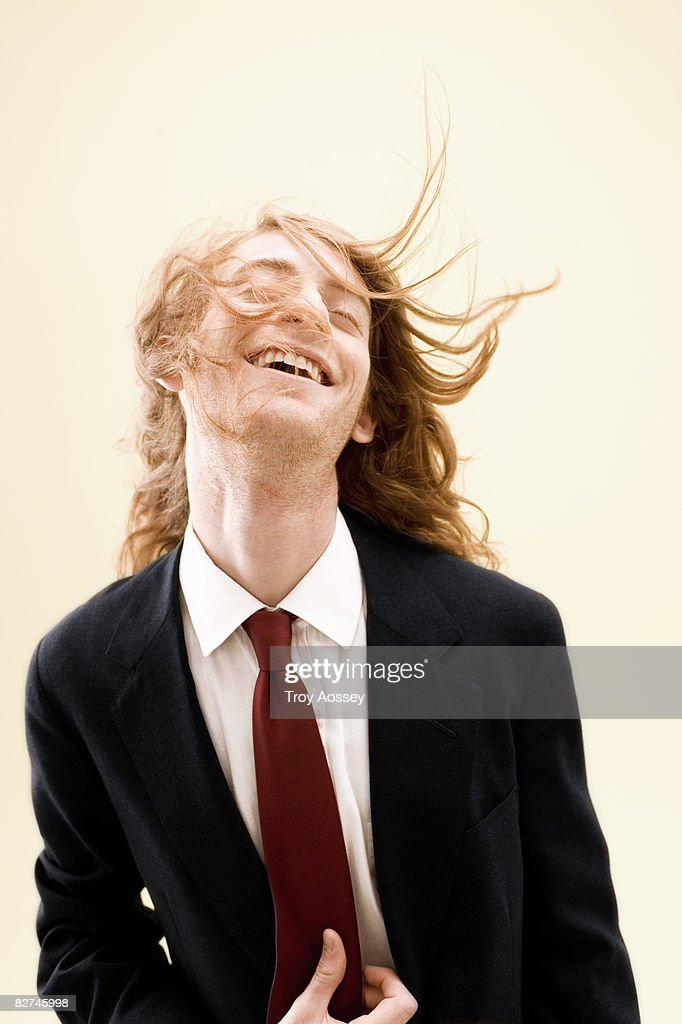 young man wearing suit with unruly hair smiling  : Stock Photo