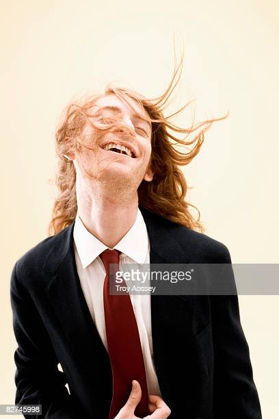 young man wearing suit with unruly hair smiling