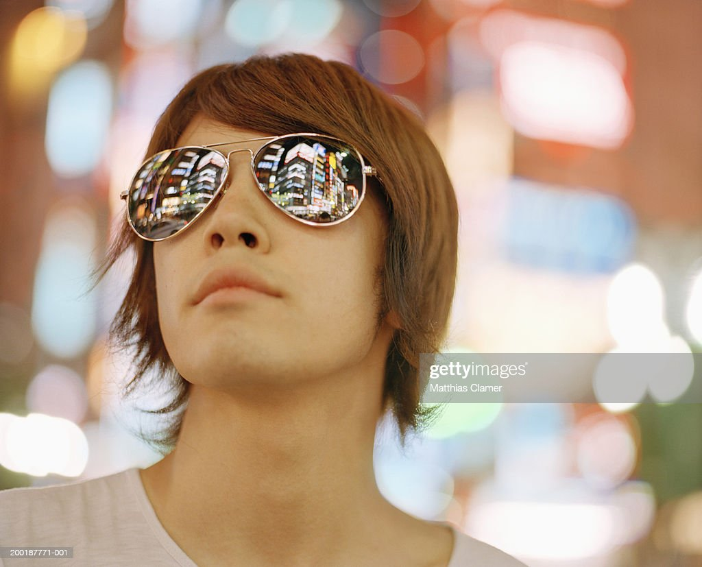 Young man wearing sunglasses, close-up signage reflected in glasses : Stock Photo