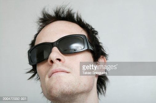 Young man wearing sunglasses, head back : Stock Photo