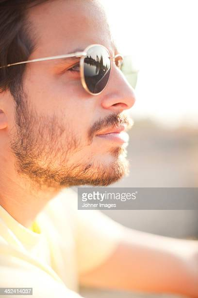 Young man wearing sunglasses looking away