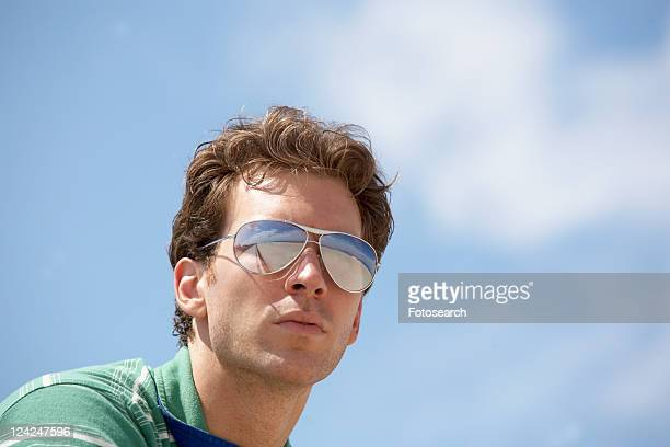 Young man wearing sunglasses (low angle view)