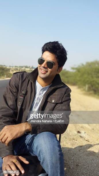 Young Man Wearing Sunglasses While Sitting On Roadside Against Sky